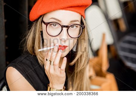 Portrait of a young stylish woman in red beret and eyeglasses smoking a cigarette