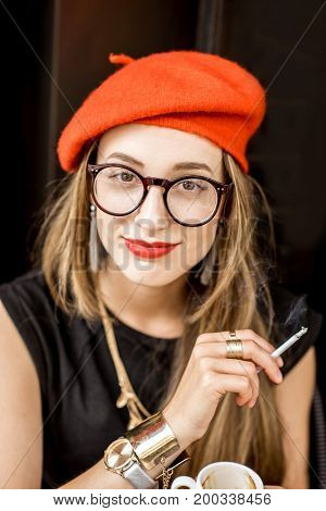 Close-up portrait of a young stylish woman in red beret and eyeglasses smoking a cigarette