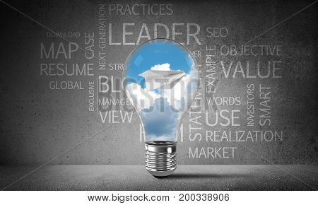 Lightbulb with flying paper plane and clouds inside placed against business related terms on grey wall on background. 3D rendering.