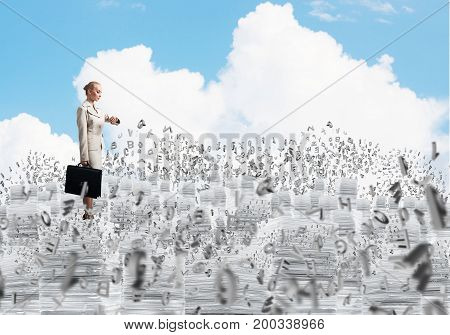 Confident business woman in suit standing on pile of documents among flying letters with cloudly skyscape on background. Mixed media.