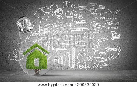 Lightbulb with green house sign inside placed against sketched business plan information on grey wall. 3D rendering.