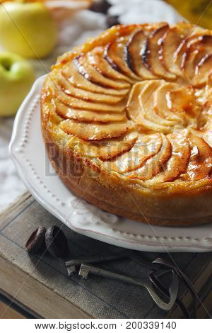 Apple tart on a background with books apples and autumn leaves.