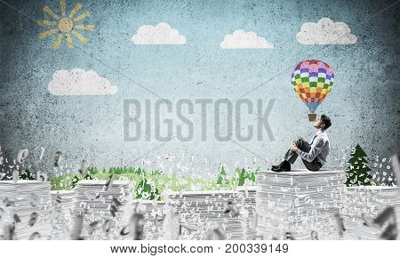Thoughtful businessman looking away while sitting among flying letters with drawn landscape background. Mixed media.