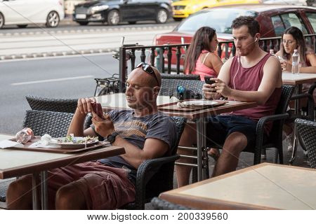 BUDAPEST HUNGARY - AUGUST 11 2017: two young caucasian men using their smartphones while sitting at bar tables in the center of Budapest Hungarian capital city