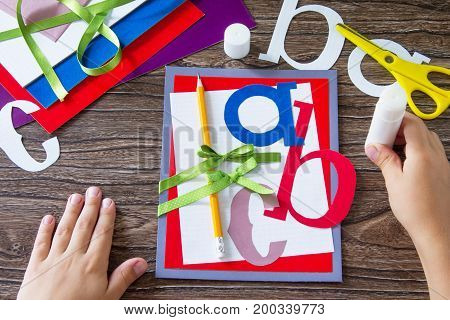 The Child Glues The Details Of The Application. Greeting Card With A Pencil And Letters For The New
