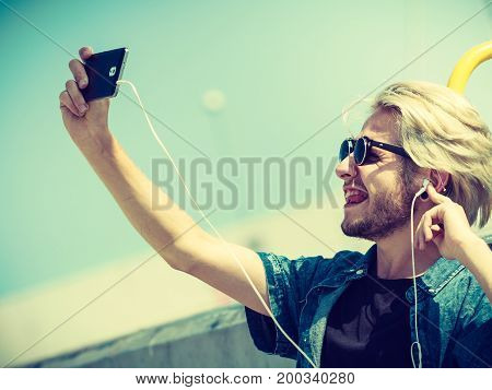 Contacts technology self-esteem concept. Young blonde man on vacations using his smartphone to take cool selfie shot sticking tongue out