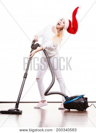 Woman vacuuming the house. Funny teen girl in santa helper hat with vacuum cleaner. Christmas time and housework concept.