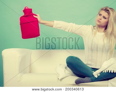 Woman Sitting On Couch Holding Hot Water Bottle