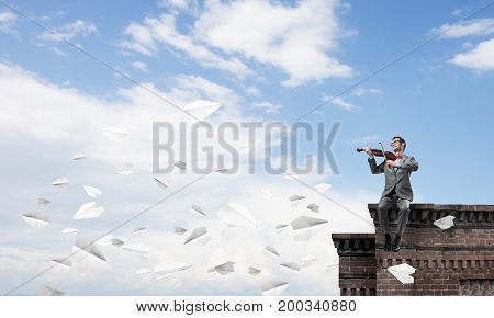 Young man wearing suit and glasses sitting on roof and playing violin