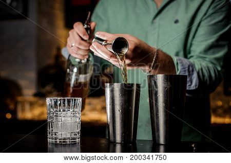 The bartender pours alcohol in a bar. Two shakers a bottle a jiger and a glass with ice