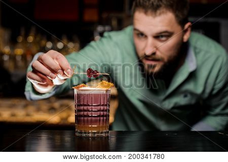 The barman decorates his cocktail. Work as a hobby. The process of completing cocktail preparation New York sour