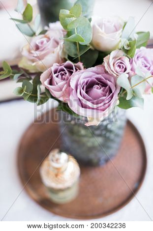 Pastel purple, mauve color fresh summer roses in vase and perfume in tray closeup, vintage style