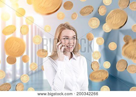 Portrait of a young blonde businesswoman wearing a white shirt talking on a smartphone and smiling. She is standing in an office under a bitcoin rain. Toned image