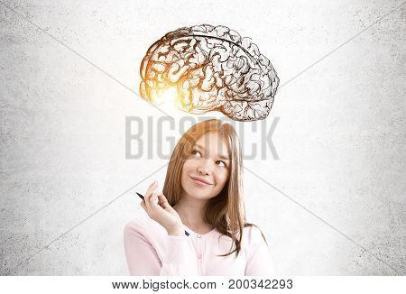 Portrait of a pensive and cheerful young woman with fair hair wearing a pink cardigan and standing near a concrete wall with a brain sketch on it. Toned image