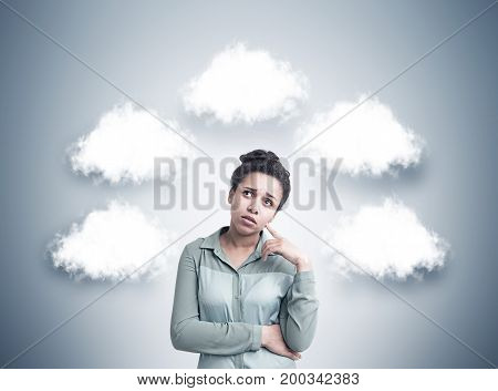 Dreamy African American woman wearing a blue shirt is standing near a gary wall with thought clouds surrounding her. Mock up