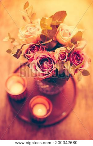 Pastel purple, mauve color fresh summer roses in vase with white wall background and candles, vintage style