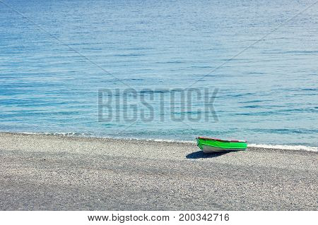Simply a green boat docked in a stoned beach in Sicily Italy