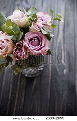 Pastel purple, mauve color fresh summer roses in vase with black tabletop board background, vintage style rustic wedding decor