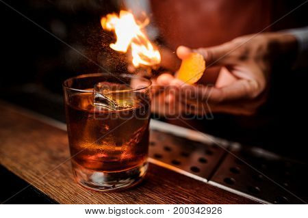 The bartender makes flame over a cocktail with orange peel close up