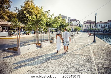 Beautiful stylish pair of European looks A young lovers couple walks holding hands Girl in a long dress A couple walks through the streets of the city