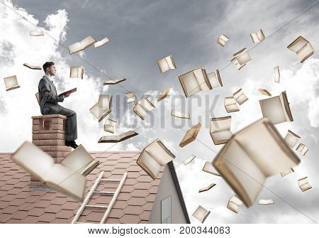 Young businessman sitting on house roof with red book in hands