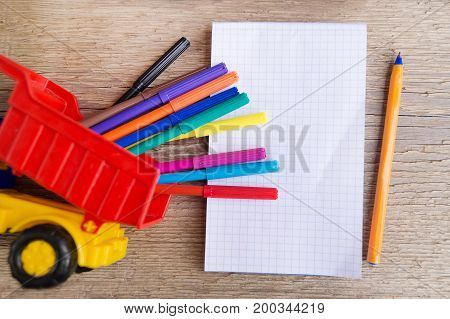 Open white notepad with colorful felt-tip pens and ball pens on the wooden table. Space for text