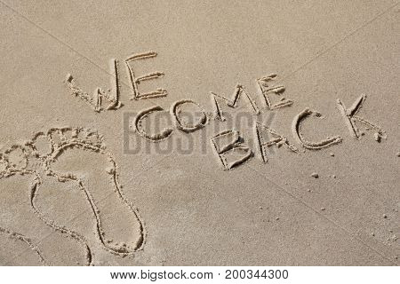 We come back - written by hand in sand on a sea beach with a soft wave. End of rest holiday