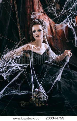 Dark beautiful woman in black dress. Halloween concept
