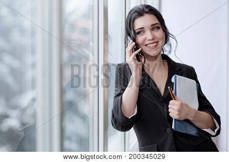 Girl in office speaking on mobile phone holding pen with notes and laughing