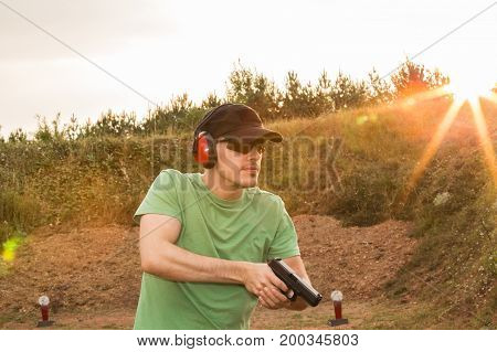Caucasian Military Soldier Or Special Force Unit Or Policeman Training On The Field With The Pistol
