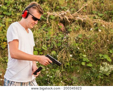 Handsome Young Blonde Guy Training On The Battlefield And Changing Magazine With Bullets On His Gloc
