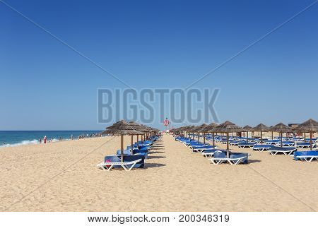 Summer morning on the beach of Tavira Island. Empty beds in the sand.