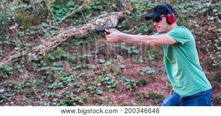 Young and handsome policeman special force muscle training with pistol glock and protective gear aiming to shot the enemy at target in the nature with black sunglasses. Fighting criminal violence