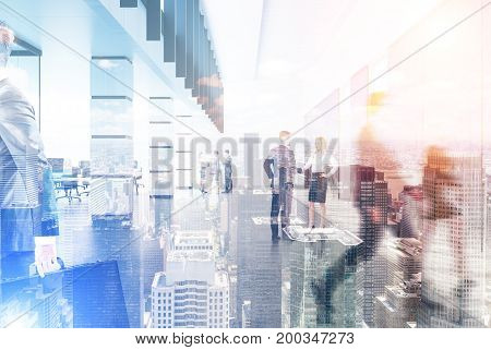 Business people walking in a busy company lobby. There is a cityscape in the foreground. Toned image double exposure