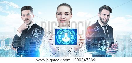 Three business partners two men and a woman are standing together and portraying success in a morning city. A woman is holding a tablet computer with an HR HUD. Toned image double exposure