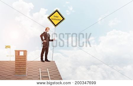 Man holding safety sign indicating under construction notice. Mixed media
