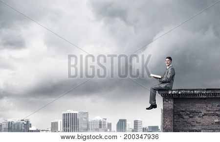 Young businessman sitting on building top with red book in hands
