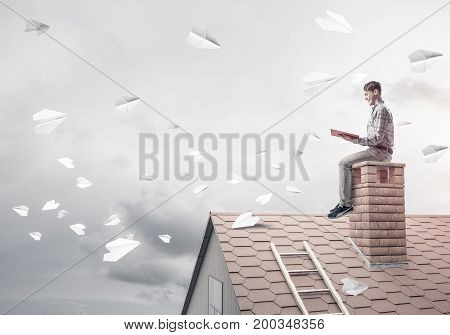Young man sitting on house with red book in hands