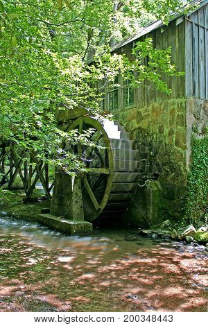 the wheel of a small gristmill by a stream in the woods