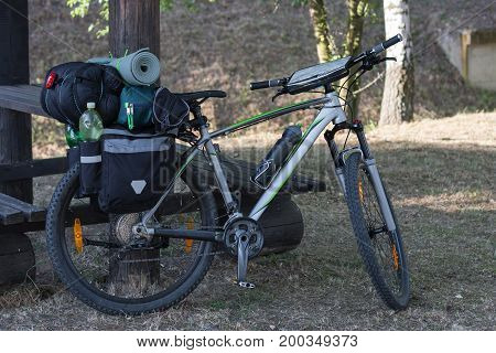 Mountain bike with saddlebags in the summer day. Camping equipments is mounted on the bike.