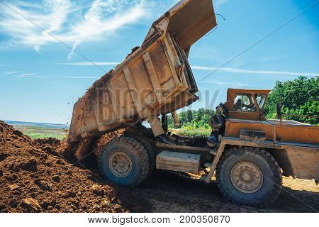 Big yellow truck unloads clay in a quarry
