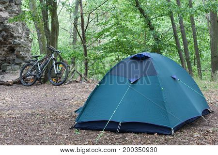 Tourist Camping Tent In The Woods, Bike Of Traveler Is In The Background.
