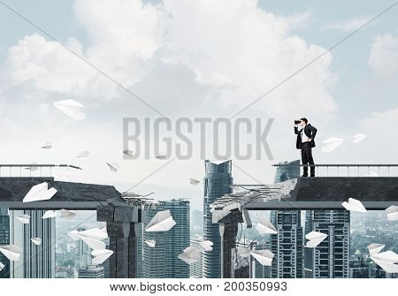Businessman in suit looking in binoculars while standing among flying paper planes on broken bridge with cityscape on background. 3D rendering.