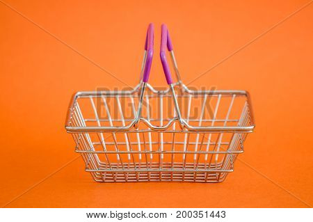 Miniature shopping basket on an orange background
