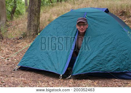 Caucasian topless man gets up in the morning in his camping tent in the woods