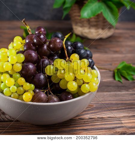 Close Up Bowl Of Various Grapes: Red, White And Black Berries On The Dark Wooden Table With Wicker B