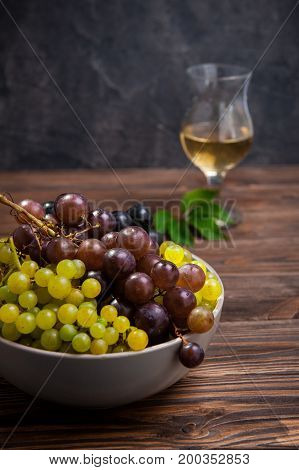 Close Up Bowl Of Various Grapes: Red, White And Black Berries On The Dark Wooden Table With Glass Of