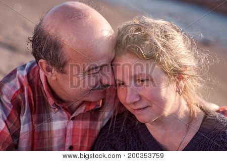 Portrait of a happy romantic couple outdoors. They sit on sea shore on sunset
