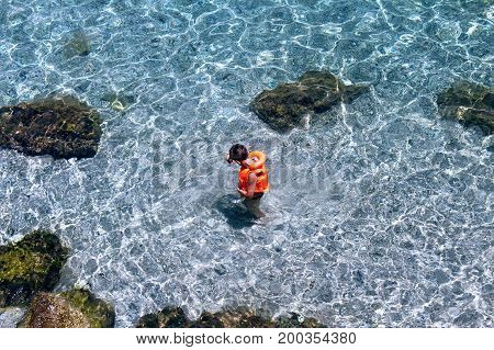 A boy in an orange lifejacket stands in crystal clear water (Alanya, Turkey).
