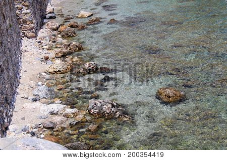 Rocky shore and crystal clear water near the fortress wall (Alanya, Turkey).